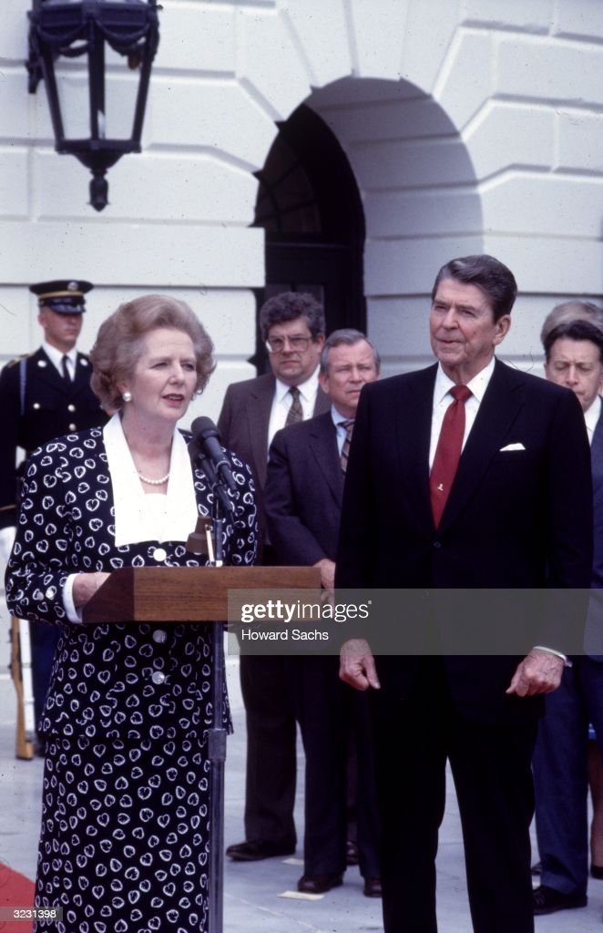 British prime minister Margaret Thatcher speaks at a podium outdoors during a visit to the White House, Washington, DC. US president Ronald Reagan stands by.