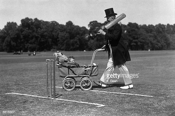 A cricketer going out to bat whilst pushing a baby in a pram at the start of the match between Licensed Victuallers and Tradespeople at Dartford