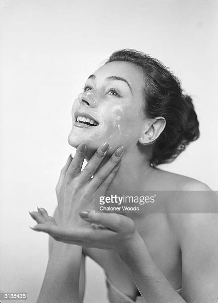 A woman applies cream to her face and neck