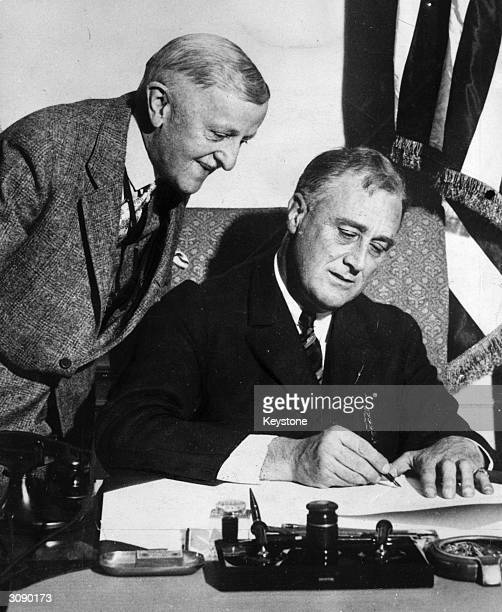 President Franklin D Roosevelt watched by the Secretary of the Treasury William Woodin as he signs the Emergency Banking Bill which makes him virtual...