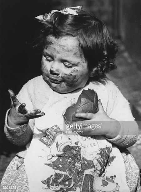 A little girl covered in chocolate as she tackles an Easter egg