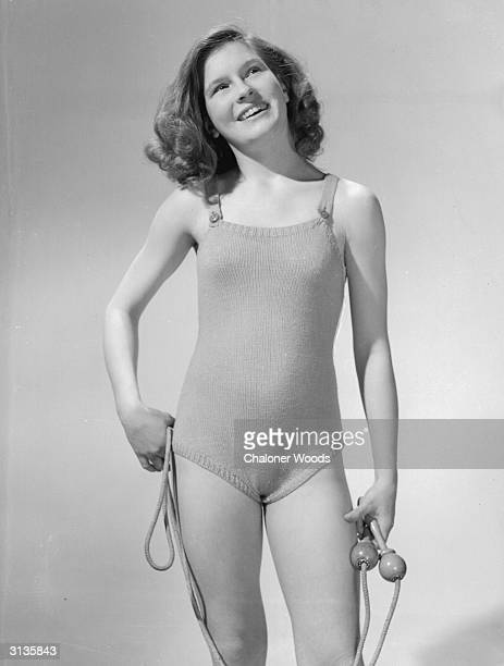 A young model with a skipping rope wearing a knitted swimsuit knitted in stocking stitch and with buttoned shoulder straps