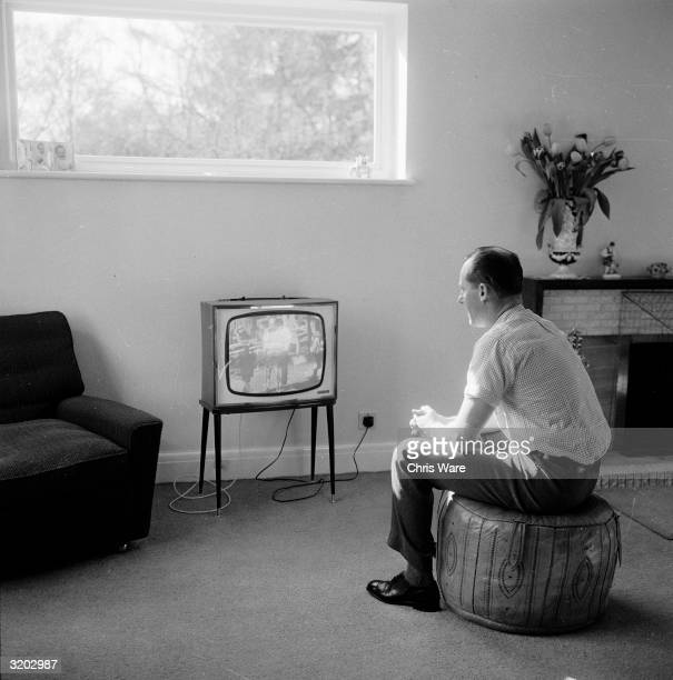 Australian jockey Ron 'The Happy Horseman' Hutchinson sits on a pouf watching horse racing on television at his home in Kingswood Surrey