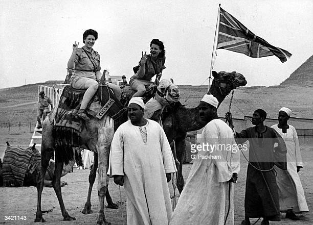 Girls from Britain's Auxiliary Territorial Services girls flaunt the 'V for Victory' sign as they ride on camels during the VDay celebrations in Cairo