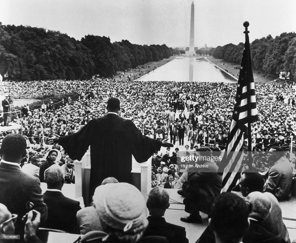 Back view of American civil rights leader and Baptist minister Martin Luther King Jr dressed in black robes and holding out his hands towards the...