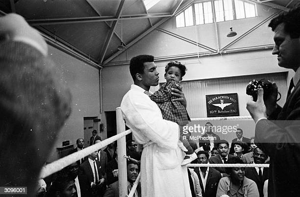 World heavyweight boxing champion Muhammad Ali meets 8 month old Maria Morin in a training session at the Territorial Army Gymnasium at White City...