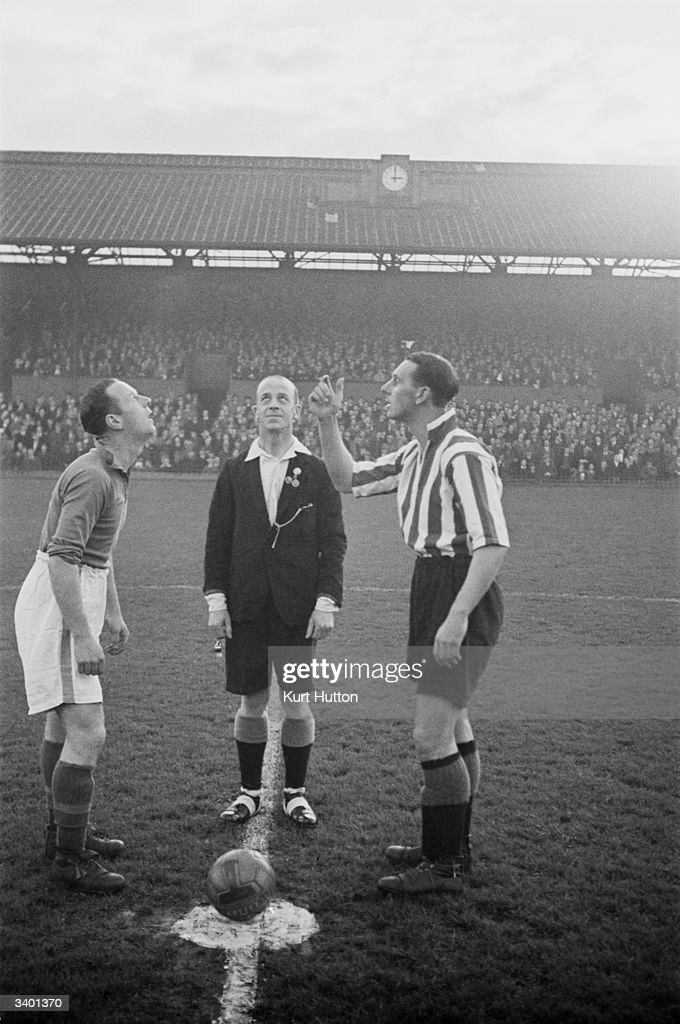 The Sunderland captain Lockie tosses the coin to decide which end they will play towards while Norman Greenhalgh and the referee looks on. Original Publication: Picture Post - 3030 - When Everton Play Away - pub. 1945