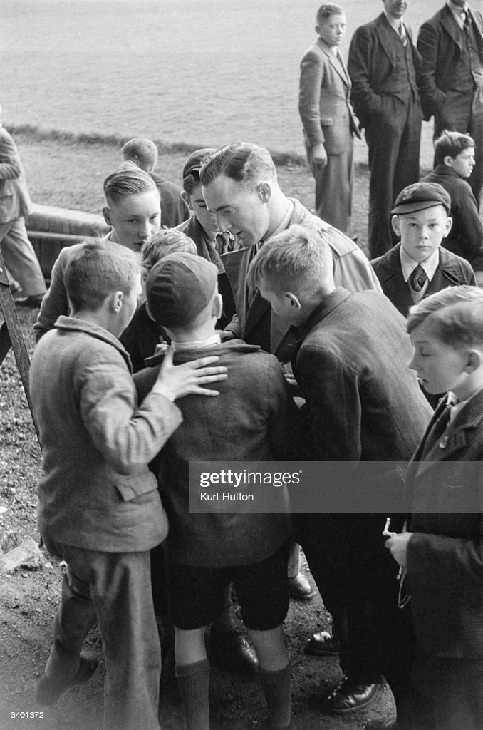 Young football fans crowd around Everton goalkeeper Burnett to ask for his autograph. Original Publication: Picture Post - 3030 - When Everton Plays Away - pub. 1945