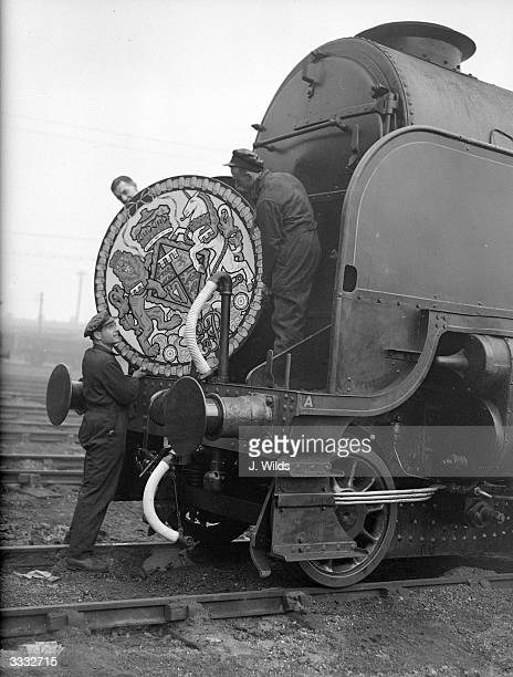 Men attaching a crest to the royal train which will be used by Princess Elizabeth and Prince Philip on their honeymoon