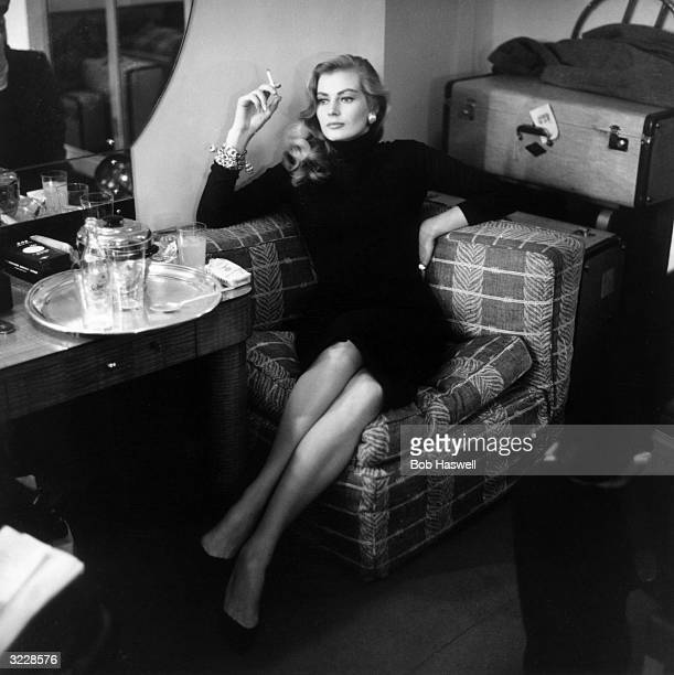 Swedish actress Anita Ekberg relaxes with a cigarette in London