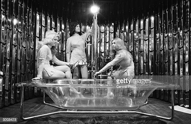 Models Jackie Robinson BarbaraAnna Milner and Maureen Tibble with a transparent Carron Constellation bathtub on display at the International Building...