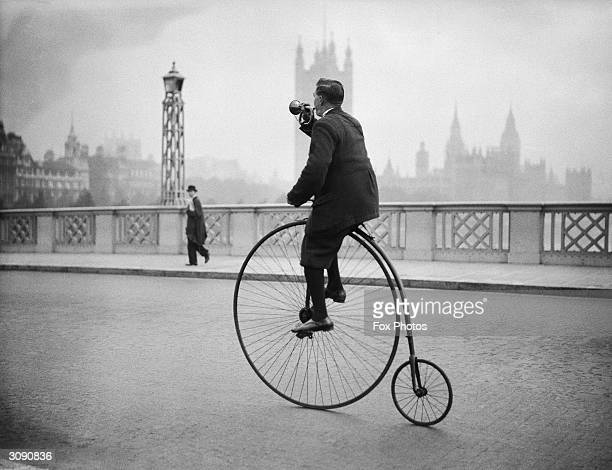 Edwin Davey riding a penny farthing bicycle over Lambeth bridge in London and blowing a bugle to warn of his approach