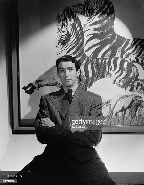 American actor James Stewart poses in front of a painting of two zebras