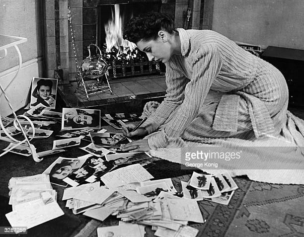 Actress Kay Kendall signs studio portraits before a cosy fire in answer to all her fanmail Kay married Rex Harrison in 1957
