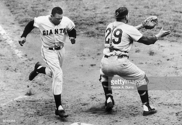 NY Giants baseball player Willie Mays crosses home plate after hitting a home run as Philadelphia Phillies Catcher Stan Lopata waits for the throw...