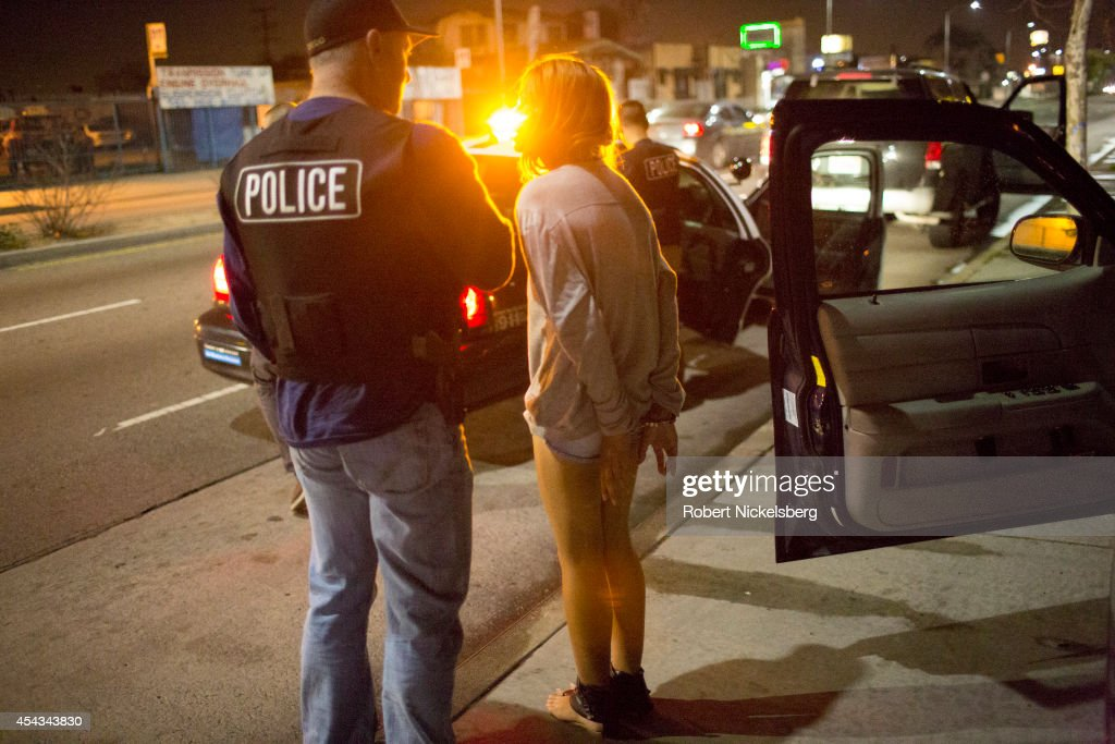 A 17year old girl in handcuffs is questioned February 2 2013 by a vice squad policeman Sergeant Brian Gallagher with the Los Angeles Police...