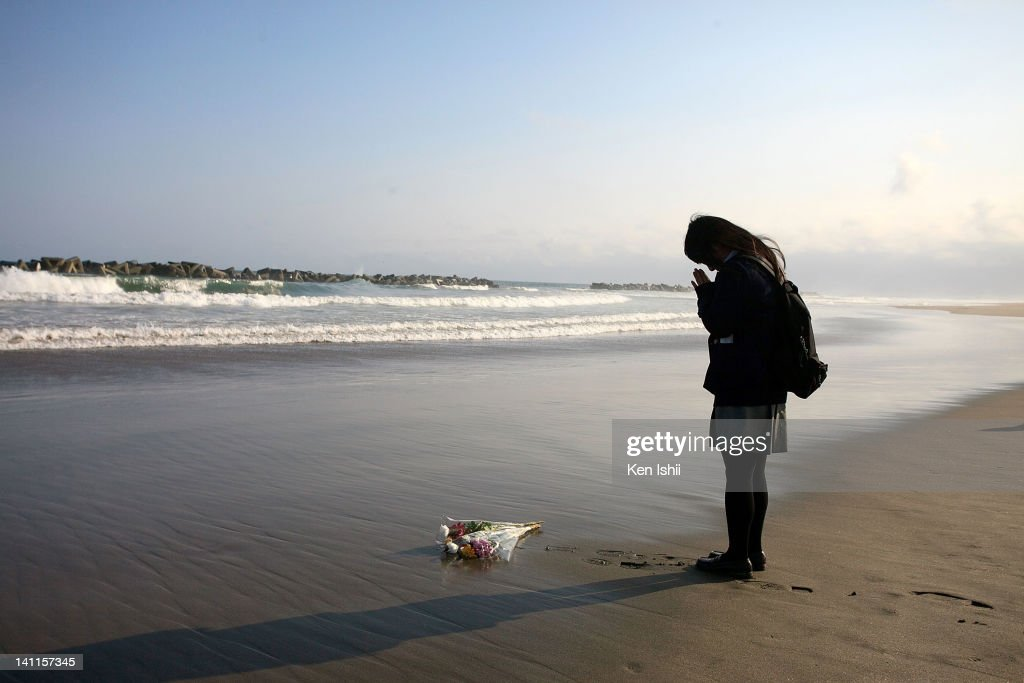 17-year-old Mai Otomo, who lost her father by last year's tsunami, places a flower bunch and prays at Arahama beach on March 11, 2012 in Sendai, Miyagi, Japan. On the one year anniversary, the areas most affected by last year's March 11, 2011 earthquake and subsequent tsunami that left 15,854 dead and 3,155 missing continue to struggle and more than 340,000 people still remain without homes living in temporary dwellings. The Japanese government faces an uphill battle with the need to dispose of rubble as it works to rebuild economies and livelihoods. Across the country people are taking part in ceremonies to pay respects to the people who lost their lives.