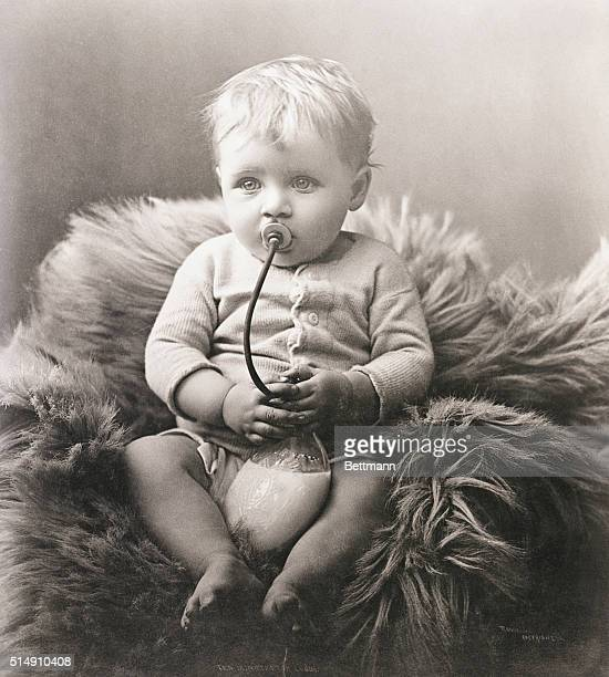 1892Baby boy on bear rug contently sucks his milk Photo by H Randall Ann Arbor
