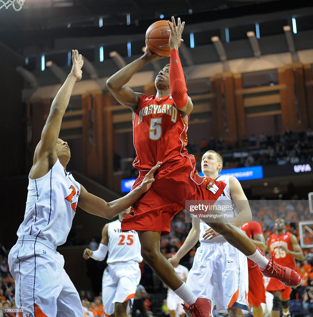 Maryland Terrapins guard Nick Faust center scores over Virginia Cavaliers forward Mike Scott right asthe University of Maryland plays the University...