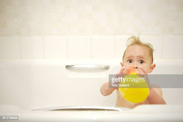 18month EllaMai HorswillRydquist looks up startled as she plays with a rubber duck in the bath