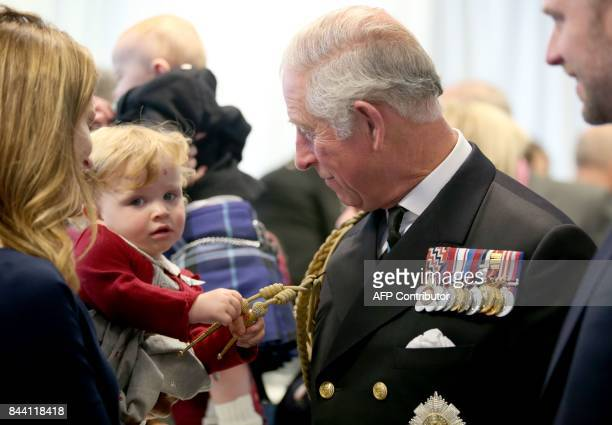 18monthold Imogen Holm pulls the braid on the uniform of Britain's Prince Charles Prince of Wales styled as the Duke of Rothesay while in Scotland at...