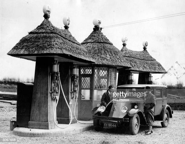 A pump attendant fills a Renault car with petrol at a garage at Blashford in Hampshire The pumps and kiosk are of unusually quaint design with...