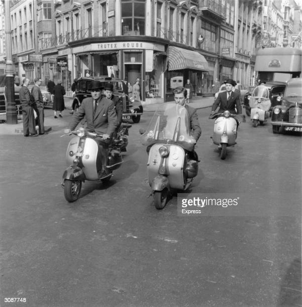 A group of businessmen riding Vespa motor scooters through the streets of London