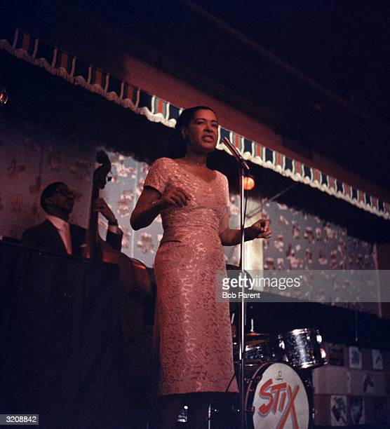 American jazz singer Billie Holiday performs on stage accompanied by a drummer and an upright bass player at the Sugar Hill nightclub Newark New...