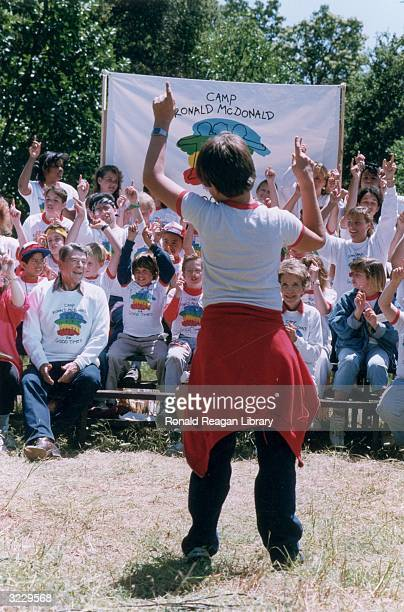 US president Ronald Reagan and First Lady Nancy Reagan sit outdoors with a group of children as a boy leads them in a song at the Ronald McDonald...
