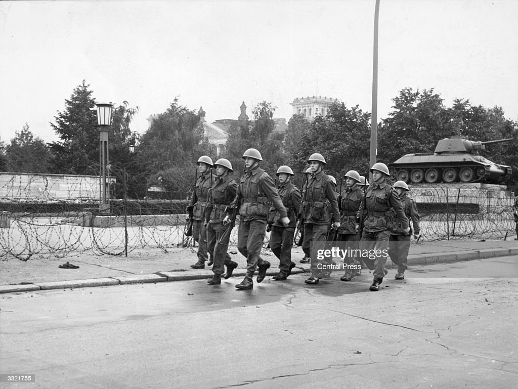 British soldiers of the King's Royal Rifle Corps (The Green Jackets) marching past the barbed wire barrier which was erected around the Russian War Memorial in the British sector of Berlin. The memorial is a focal point for demonstrations against the Communists.