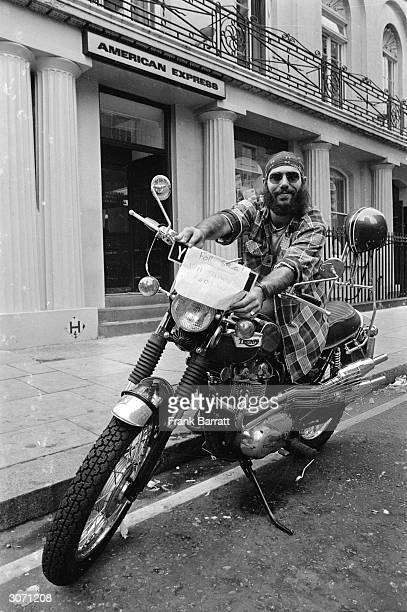 An American traveller outside the American Express offices in the Haymarket London with his motorbike which he is trying to sell to raise money...