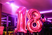 Balloons in shape of number 18 candle on a birthday party.