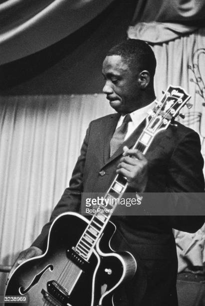 Musician Wes Montgomery stands on stage with his guitar at the Jazz Gallery New York City