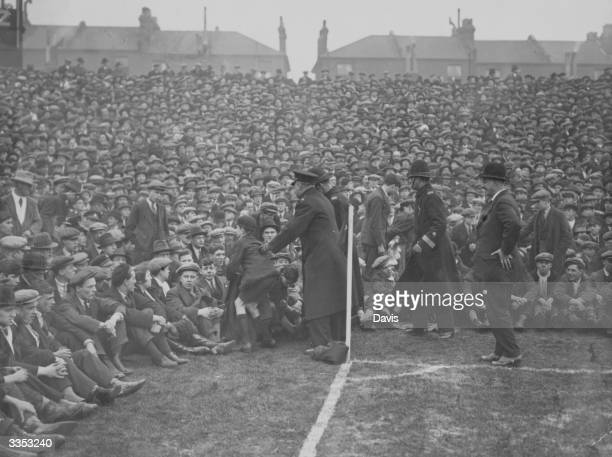 Police regulate the crowd at the touchline as great numbers of spectators crowd the pitch at Highbury in London for the cup tie battle between...