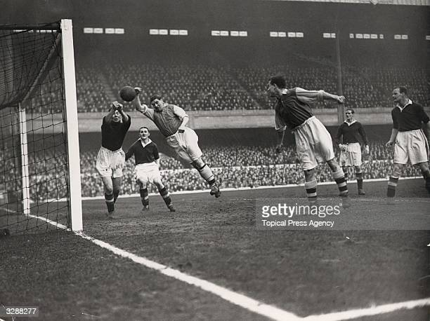 Chelsea goalkeeper Woodley dives to save a goal from Arsenal forward Drake in a football match between the two clubs