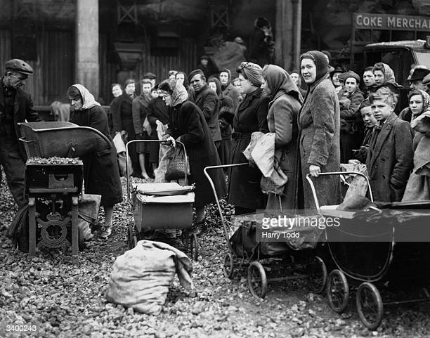 Housewives with their prams ready to take away the week's coal supply at the Nine Elms depot of the Gas Light and Coke Company in London People are...
