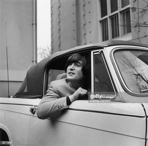 Singer songwriter and guitarist John Lennon of The Beatles in his Triumph Herald convertible car