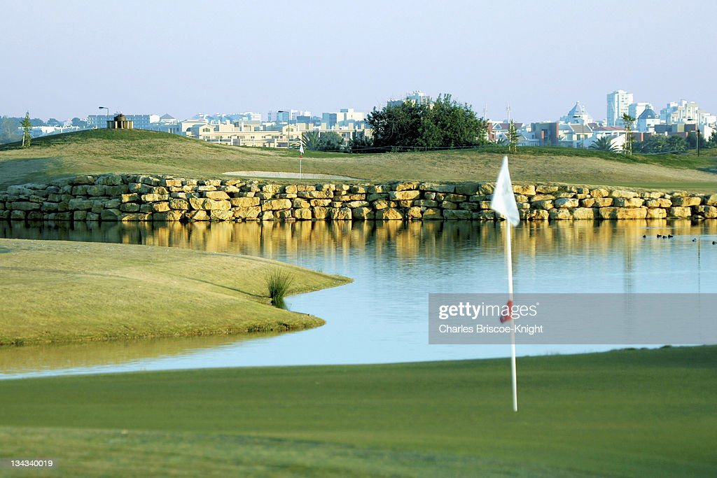 18th green at the venue for the 2005 World Cup Victoria Golf Club in Portugal's Algarve View to 14th green and the town of Vilamoura