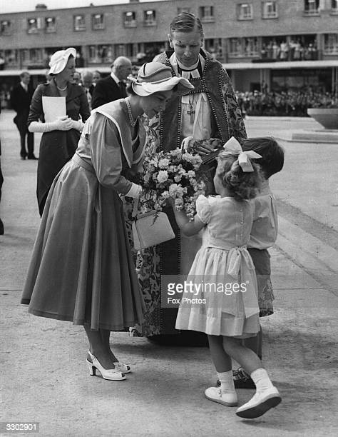 The Queen accepts a bouquet from two children Michael GresfordJones the Lord Bishop of the Diocese looks on
