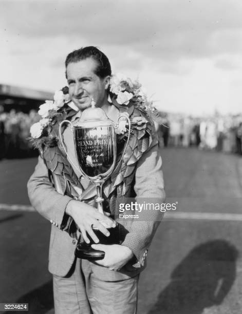 Ferrari driver Alberto Ascari holding his trophy after winning the British Grand Prix at Silverstone