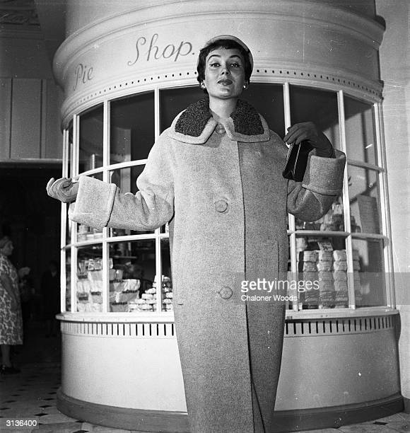 A lady standing by the pie shop in Harrods department store London wearing a long buttoned coat