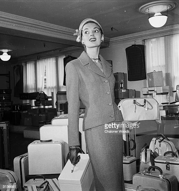 A lady wearing a tailored suit from Harrods department store London stands next to a heap of luggage
