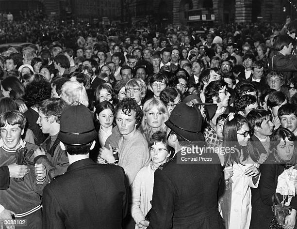 Policemen controlling over 5000 fans who flocked into London's Piccadilly Circus to see the stars arrive for the premiere of the Beatles film 'Yellow...