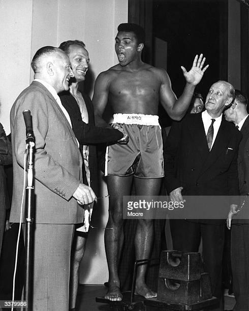 US boxer Cassius Clay and British boxer Henry Cooper weighin on the stage of the Palladium for their heavyweight match at Wembley Stadium London Clay...