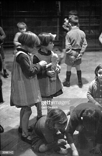 Young twin girls clutch their dollies at a Play Centre in London Original Publication Picture Post 105 Children's Play Club pub 1939