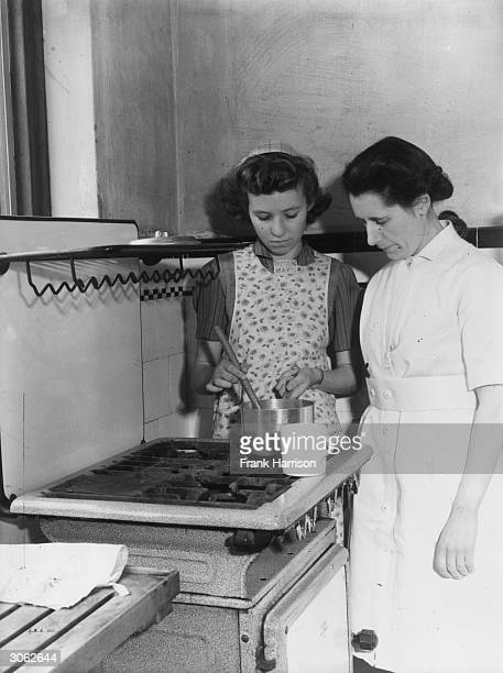 Marion Pickett a pupil at Eastwood High School Southend Essex learns how to mix a sauce from Domestic Science mistress Miss Johnson The school was...