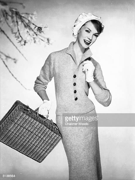 A smiling lady wearing a fitted woollen pencil skirt and matching pullover and carrying a wickerwork picnic hamper seems keen to get going Woman's...