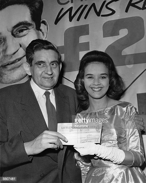 Office clerk Charlie Cooper receives a cheque for £225 his winnings from the Littlewoods Football Pools from Miss World Carol Joan Crawford in London