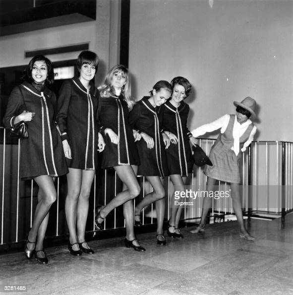 English fashion designer Mary Quant with a group of models at Heathrow Airport before leaving for a continental fashion tour