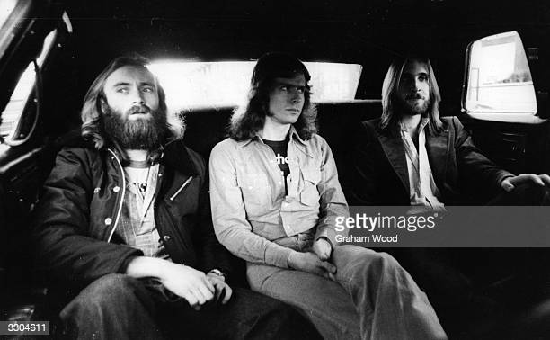 British rock group Genesis from left to right Phil Collins Tony Banks and Mike Rutherford in the back of a limousine on the way to the LA Forum where...
